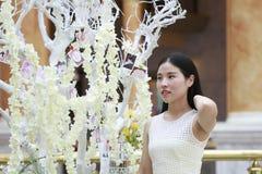 愉快地穿一件白色礼服的亚裔妇女起来她顶头微笑看 免版税图库摄影