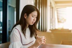 愉快地穿白色衬衫,开会,饮用的热的咖啡的亚裔美女在面包店明亮早晨 免版税库存图片