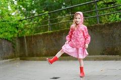 愉快地站立在雨下的可爱的女孩 免版税图库摄影
