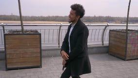 愉快地走和跳舞在街道上的年轻可爱的非裔美国人的男性特写镜头画象在都市城市 股票录像