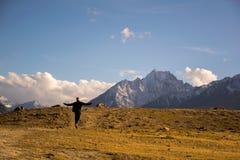 愉快地走通过山道路的人 免版税库存图片
