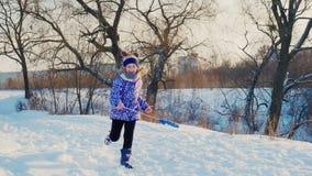愉快地跑在雪的滑稽的女孩,是冬天愉快的开始  股票录像