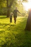 愉快地跑横跨的母亲和年轻儿子 免版税库存照片