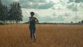 愉快地跑沿金黄领域的年轻深色的妇女在明亮的晴天 影视素材