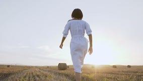 愉快地跑通过与秸杆大包的一个金黄领域的一名年轻逗人喜爱的妇女在日落 跑愉快的女孩享用和 股票视频