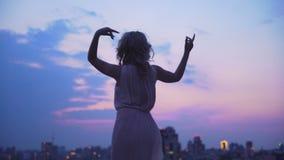 愉快地跳舞反对大都会夜空和光背景的女孩  股票录像