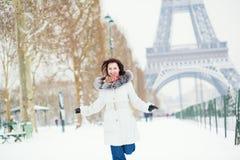 愉快地跳跃在巴黎的女孩在一个冬日 免版税图库摄影