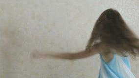 愉快地转动蓝色的礼服的美丽的女孩 影视素材