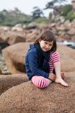 愉快女孩微笑,放松在一块巨型花岗岩石头 免版税库存图片