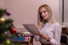 愉快女性工作在圣诞节的一个办公室 免版税库存图片