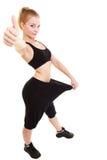 愉快妇女显示多少重量她丢失了,大裤子 库存图片