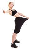 愉快妇女显示多少重量她丢失了,大裤子 免版税库存照片