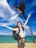 愉快妇女的背包徒步旅行者到达热带海滩 库存照片