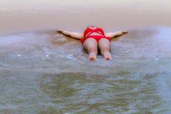 愉快妇女红色的比基尼泳装在海滩放松 免版税库存图片