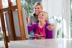 愉快妈妈绘画和女儿微笑 免版税库存照片