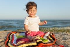 愉快婴孩微笑和挥动的手,坐在地毯的白色含沙热带海滩 免版税图库摄影