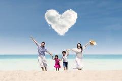 愉快家庭在爱云彩下的海滩 免版税库存图片