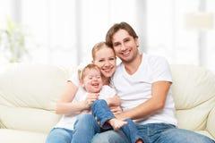 愉快家庭母亲、父亲,儿童小女儿在家使用的沙发的和笑 库存照片