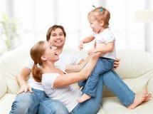 愉快家庭母亲、父亲,儿童小女儿在家使用的沙发的和笑 库存图片