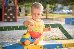 愉快微笑和英俊的男孩孩子获得使用的乐趣在操场在一个公园在明亮的晴天 库存照片