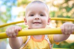 愉快微笑和英俊的男孩孩子获得使用的乐趣在操场在一个公园在明亮的晴天 图库摄影