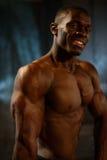 愉快微笑的优胜者黑非裔美国人的健身式样显示在演播室干涉有黑暗的背景 免版税库存照片