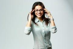 年轻愉快微笑的女实业家佩带的玻璃站立 免版税库存照片
