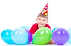 愉快微笑的boylying在与五颜六色的气球的地板上 免版税库存图片