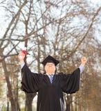 愉快成熟毕业生举行的文凭户外 免版税库存图片