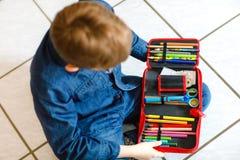 愉快搜寻在笔匣的一支笔的矮小的个学校孩子男孩 有玻璃劫掠的健康学童为教训认为 库存图片