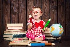 愉快有玻璃和铅笔的一个好小女孩以书和地球为背景 免版税图库摄影
