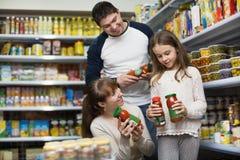 愉快正面微笑做父母与被装罐的小女孩购买 免版税库存照片