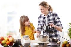 愉快母亲和cutie女儿烹调 免版税库存照片