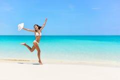 愉快比基尼泳装妇女跳跃在白色海滩的喜悦 库存图片
