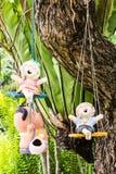 愉快泰国女孩微笑黏土的玩偶坐摇摆 免版税库存照片