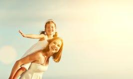 愉快海滩的系列 拥抱儿童女儿的母亲 库存图片