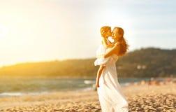 愉快海滩的系列 拥抱小女儿的母亲在日落 库存图片