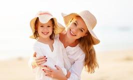 愉快海滩的系列 母亲和儿童在日落的女儿拥抱 免版税库存图片