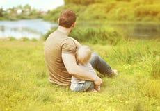 愉快父亲和儿子休息的一起坐草夏天 免版税库存图片