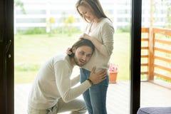 愉快爸爸对是投入耳朵给怀孕的腹部、怀孕和人 免版税库存图片
