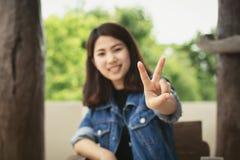 愉快牛仔裤的衣物的年轻亚裔妇女 免版税库存图片