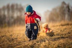 年轻愉快男孩使用室外与他的玩具熊和台车 免版税库存照片