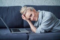 愉快白肤金发妇女说谎有倾向在沙发和研究手提电脑 库存图片