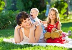 愉快的一起使用在公园的妈咪和她的孩子 室外por 免版税库存照片