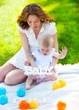 愉快的一起使用在公园的妈咪和她的孩子 库存照片
