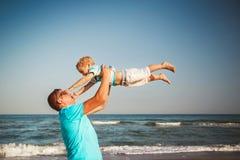 愉快的一起使用在海滩的父亲和儿子 父亲在天空中的投掷他的儿子 免版税库存图片