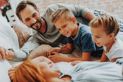 愉快的一起放松在床上的父母和孩子 库存照片