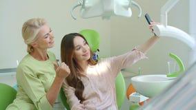 愉快的一起采取selfie的医生和患者 牙医椅子的微笑的妇女 股票录像