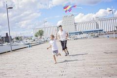 愉快的一起飞行风筝的爸爸和儿子 免版税库存图片
