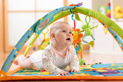 愉快的七个月女婴演奏说谎在五颜六色的playmat 免版税库存照片